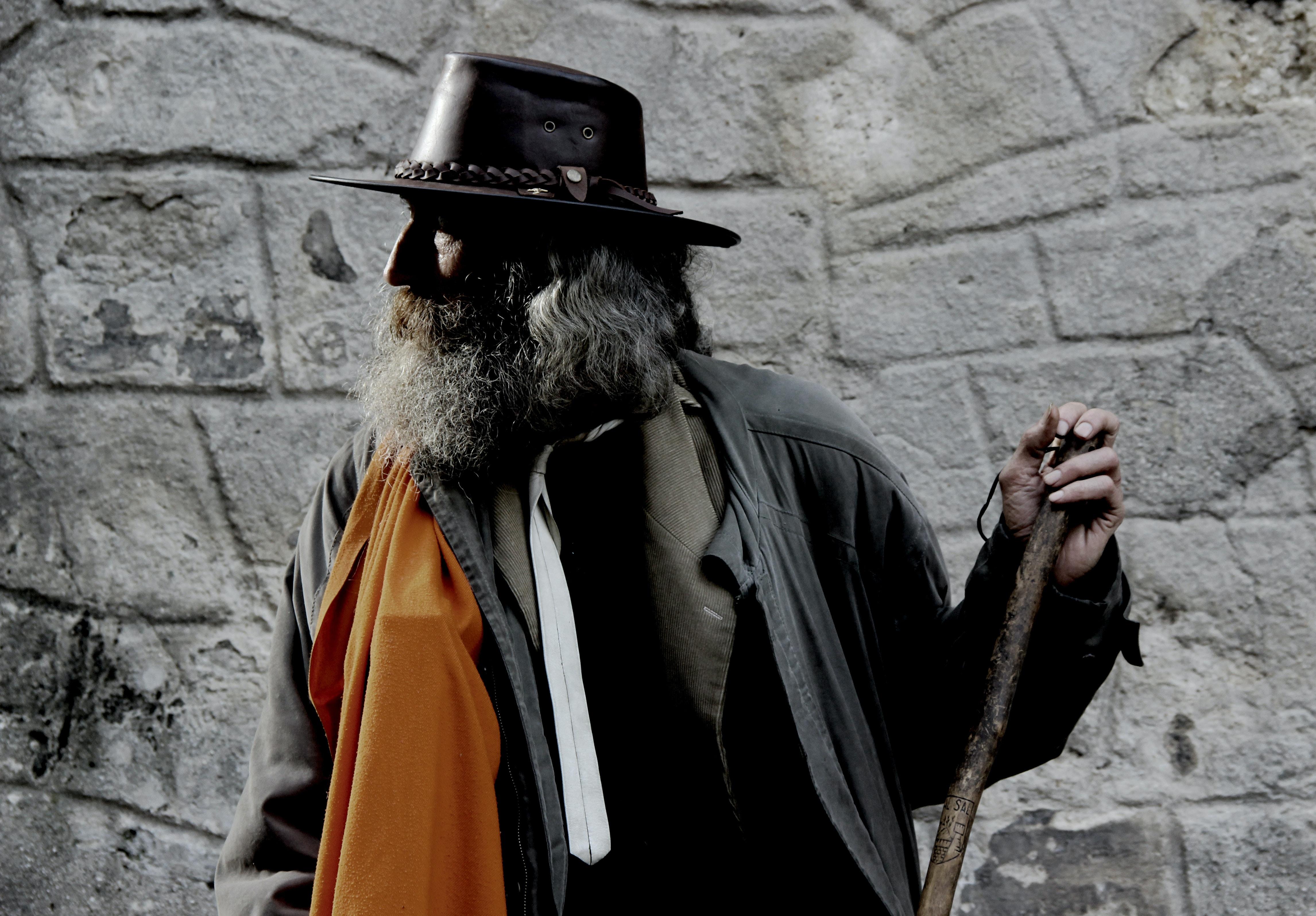 man holding walking cane behind wall