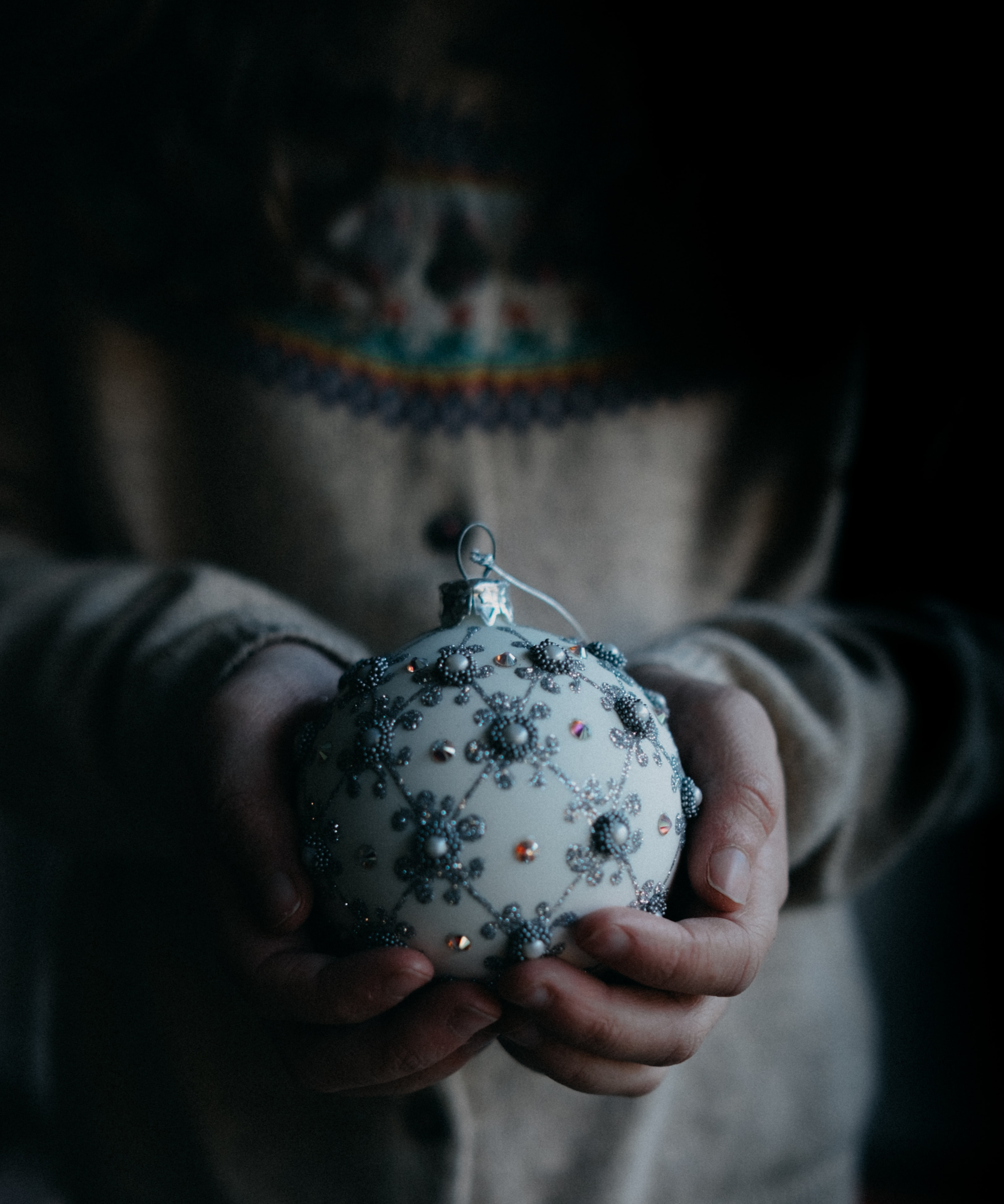 person holding white and grey ornament