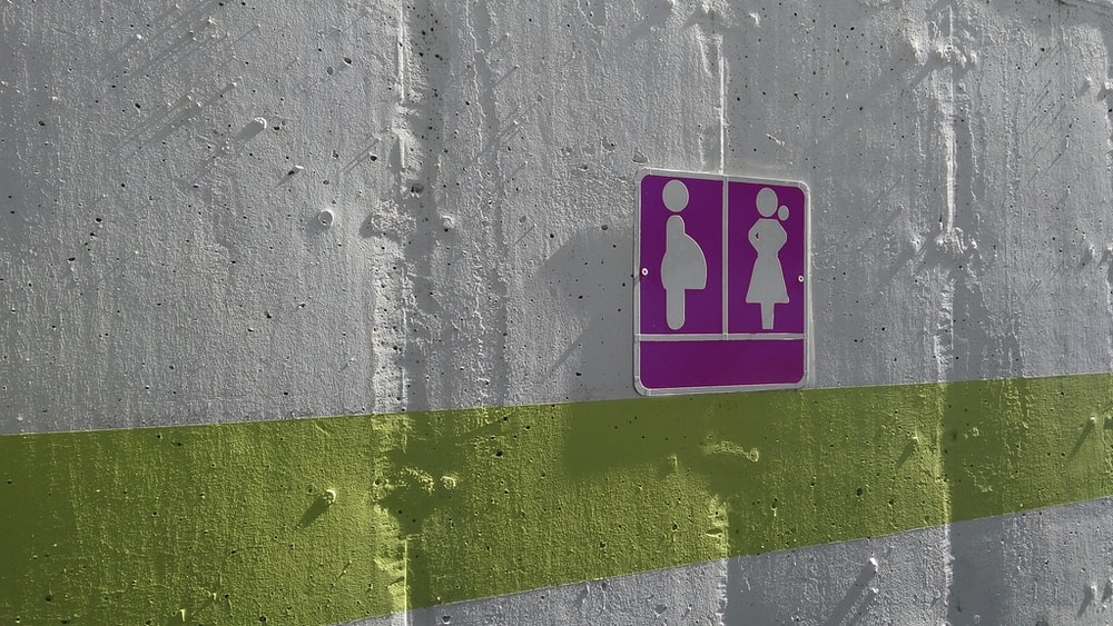 purple woman and pregnant woman signage on white painted wall