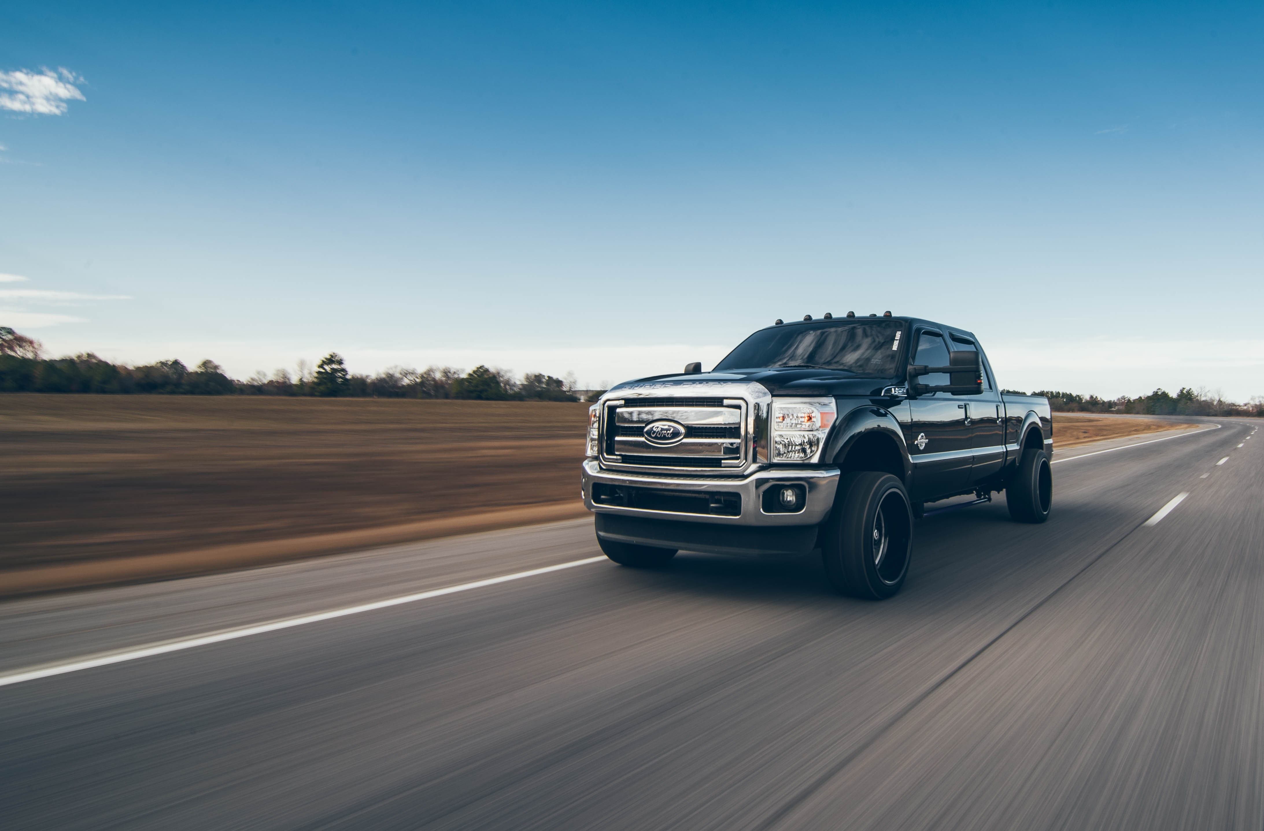 time lapsed photo of black Ford crew cab pickup truck on road
