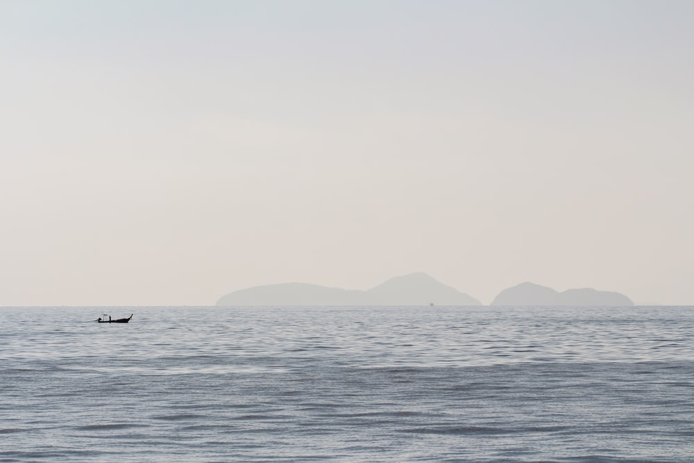 silhouette of boat sailing on ocean