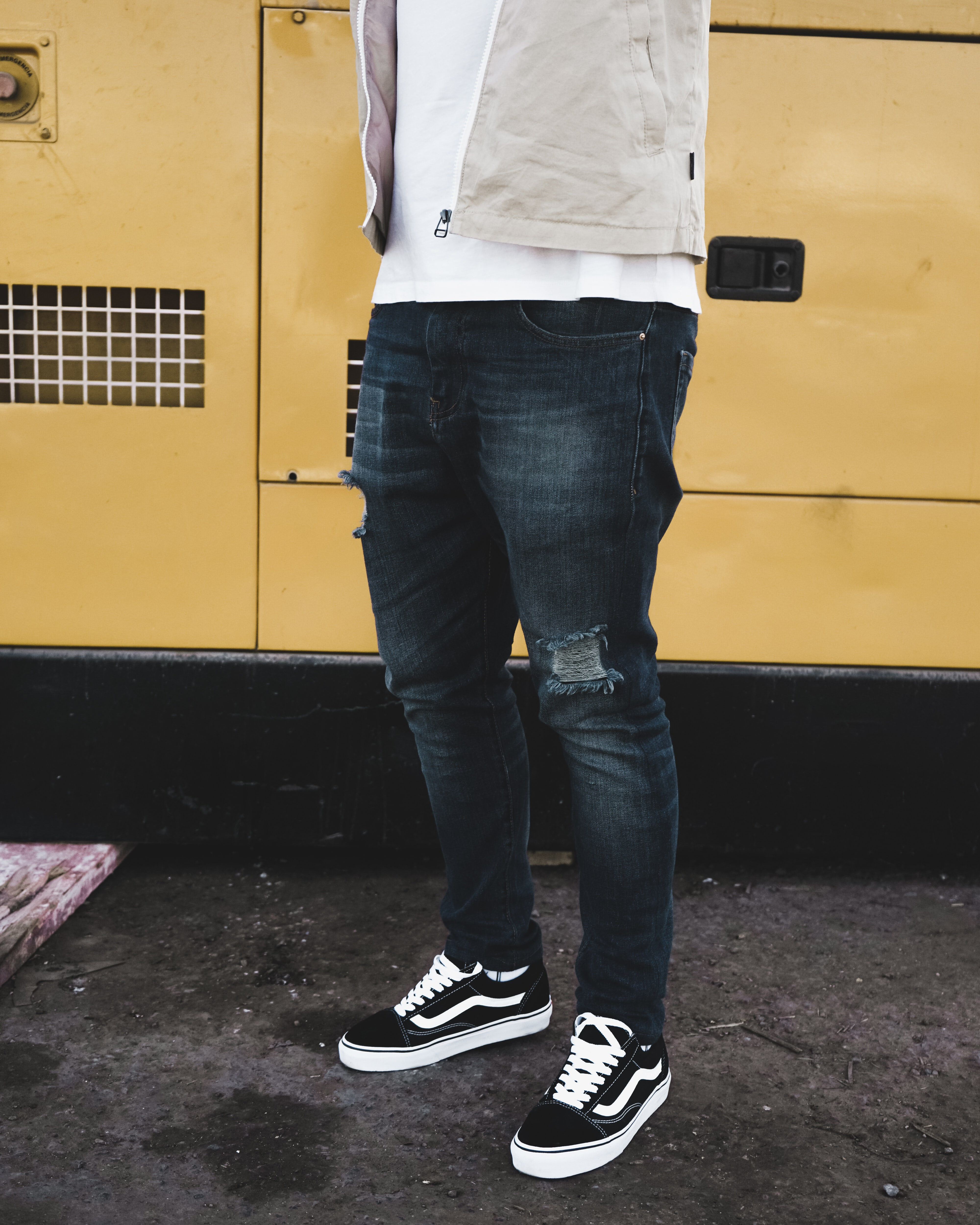 man wearing distressed black denim fitted jeans and pair of black Vans Old Skool shoes