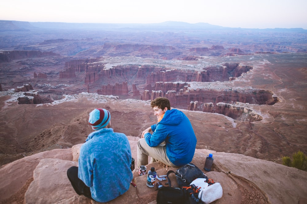 two man sitting on the edge of a cliff during daytime