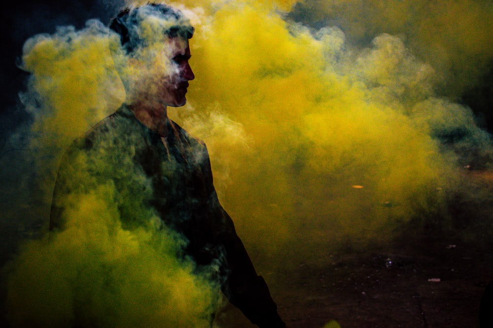 man standing surrounded by yellow smoke