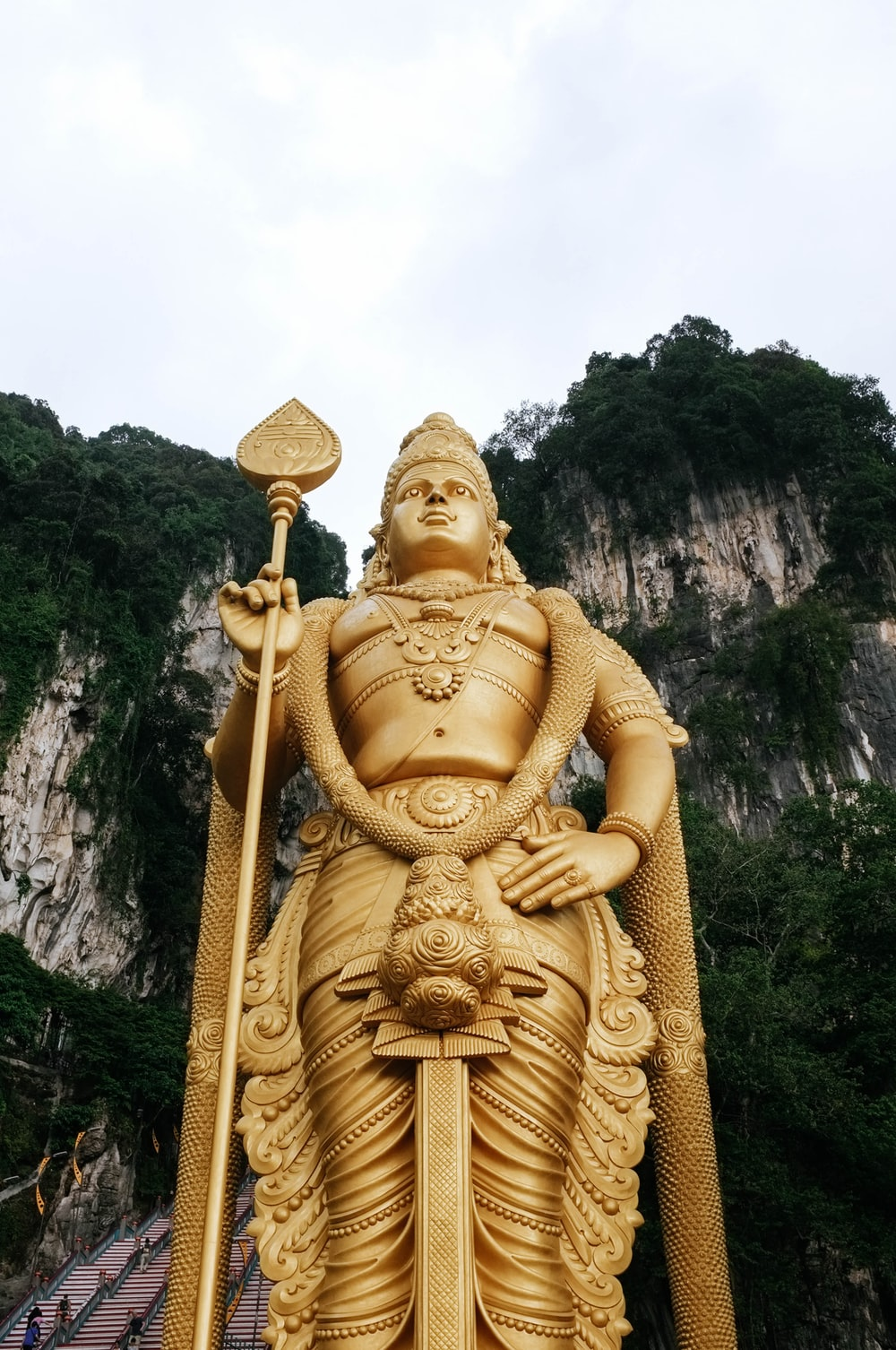 low angle photograph of Lord Murugan state near mountain cliff under cloudy sky