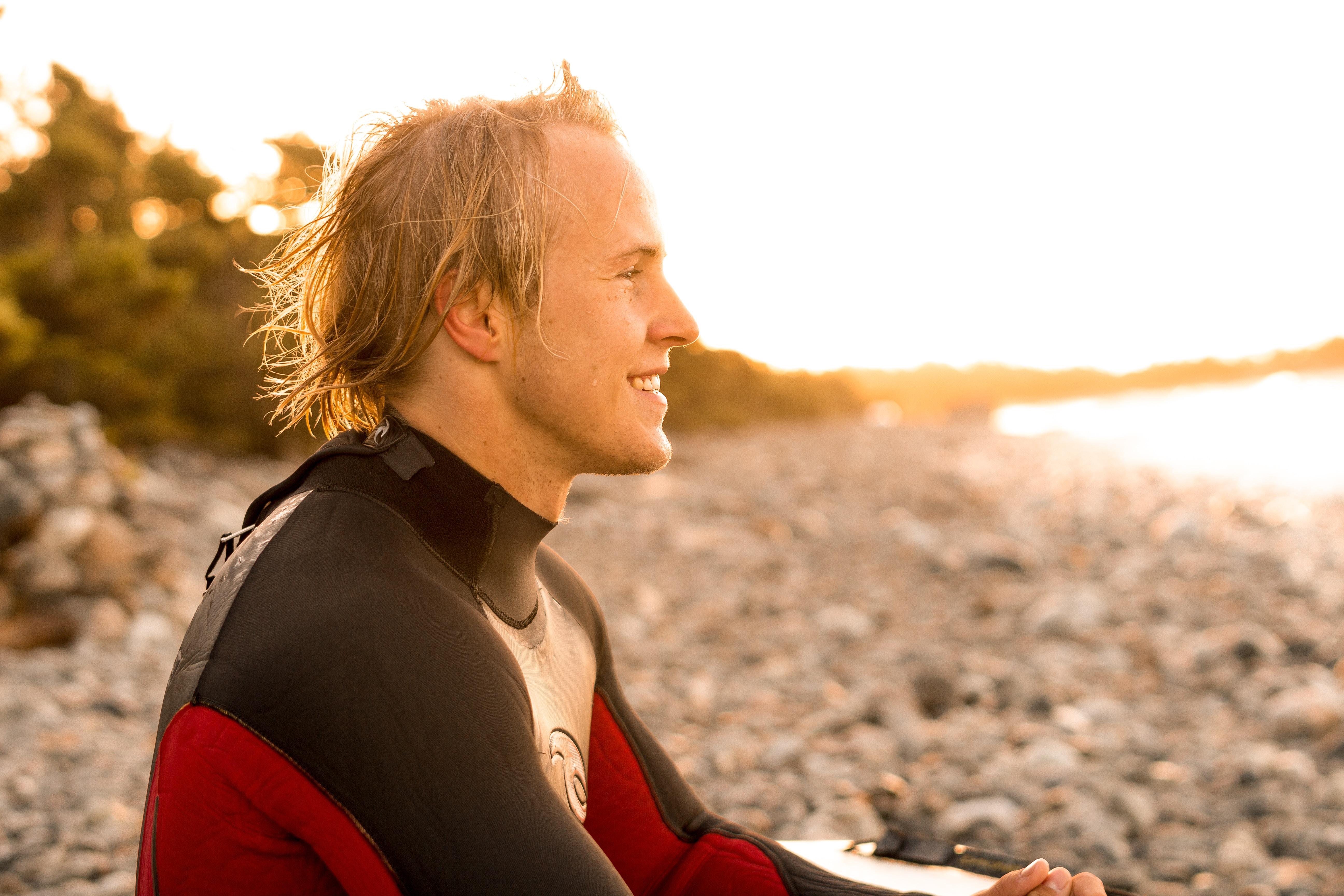 smiling man wearing wetsuit facing beach