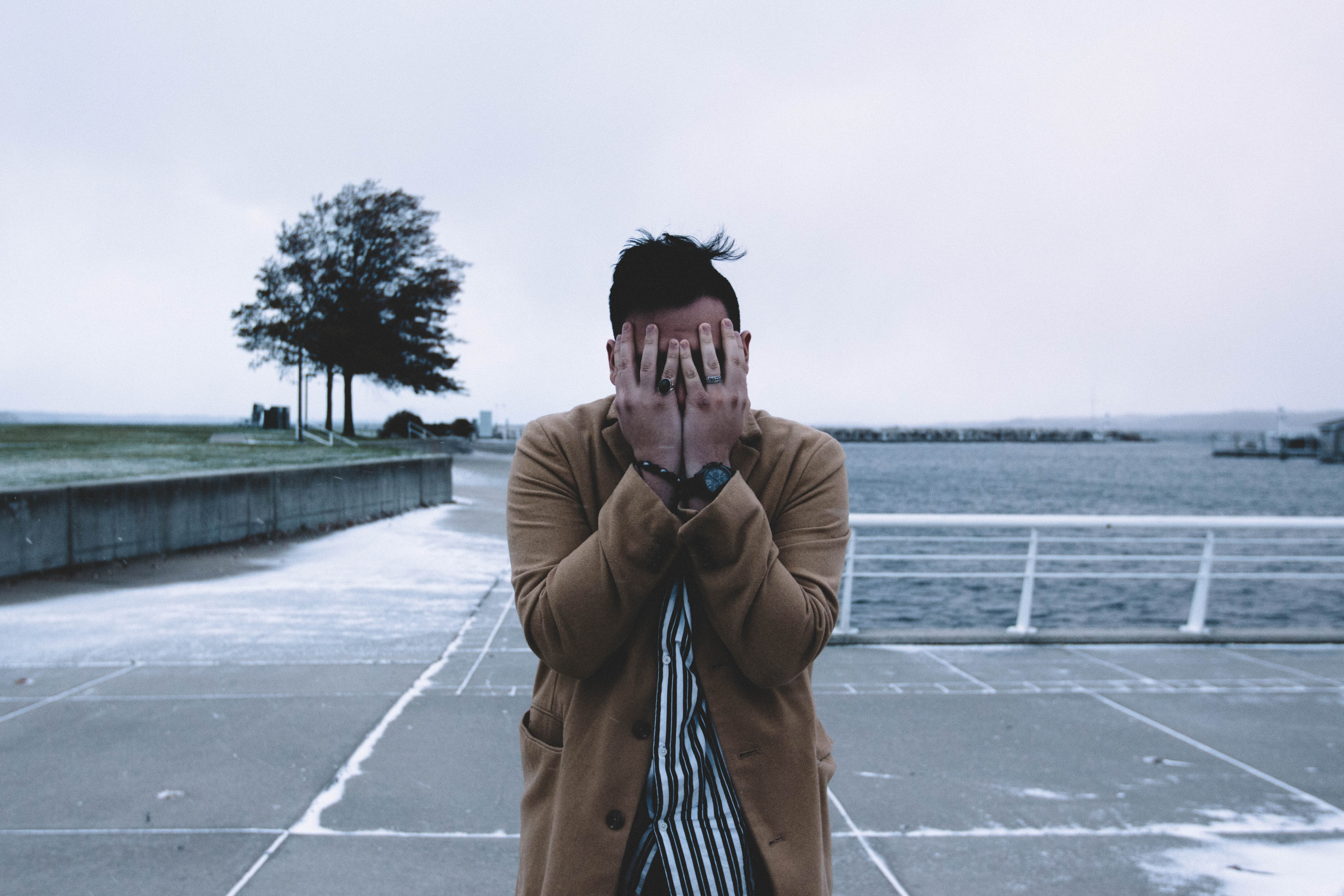 man covering face during daytime