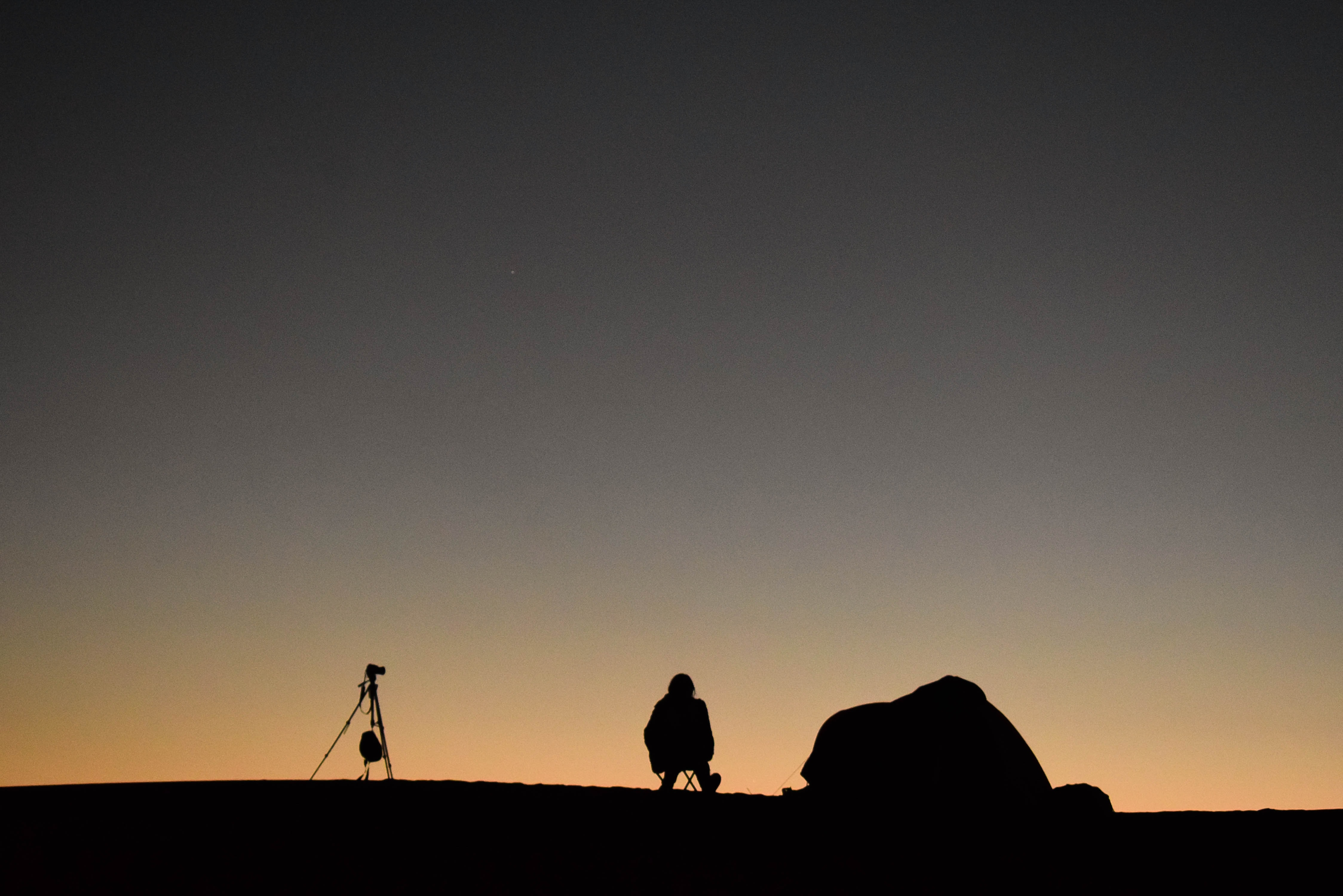 silhouette photo of person sitting on a camping chair