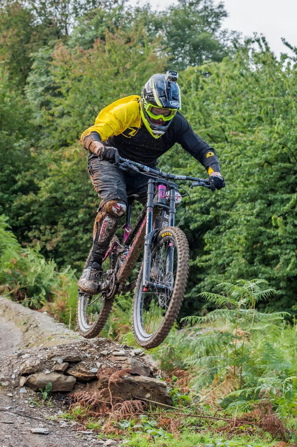 man riding on gray full-suspension mountain bicycle during daytime