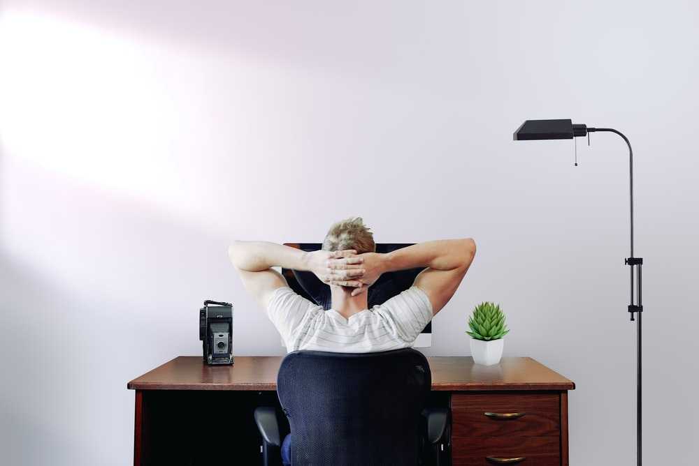 man holding his head while sitting on chair near computer desk