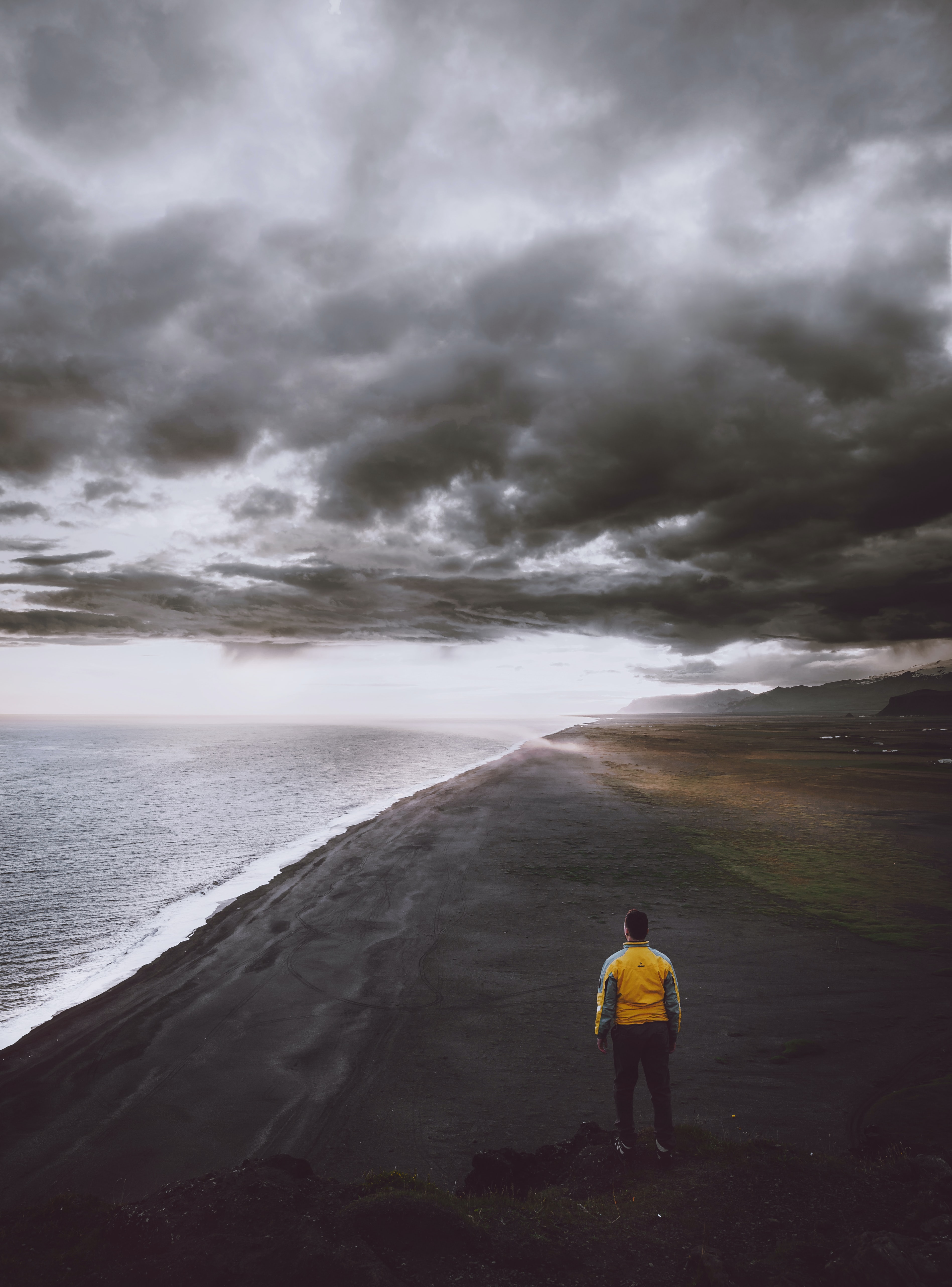 man standing on coastline under cloudy sky