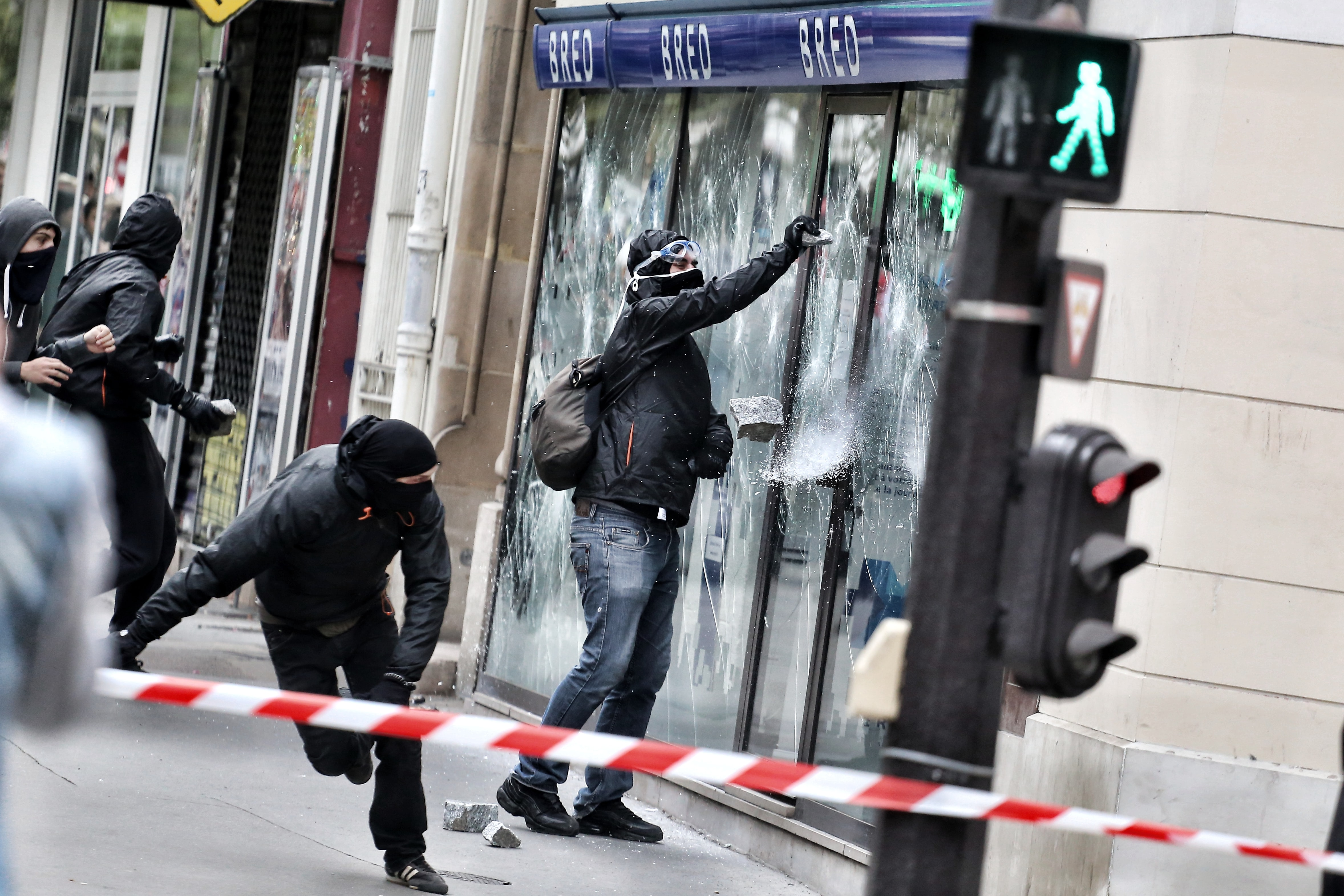 group of people breaking glass wall during daytime