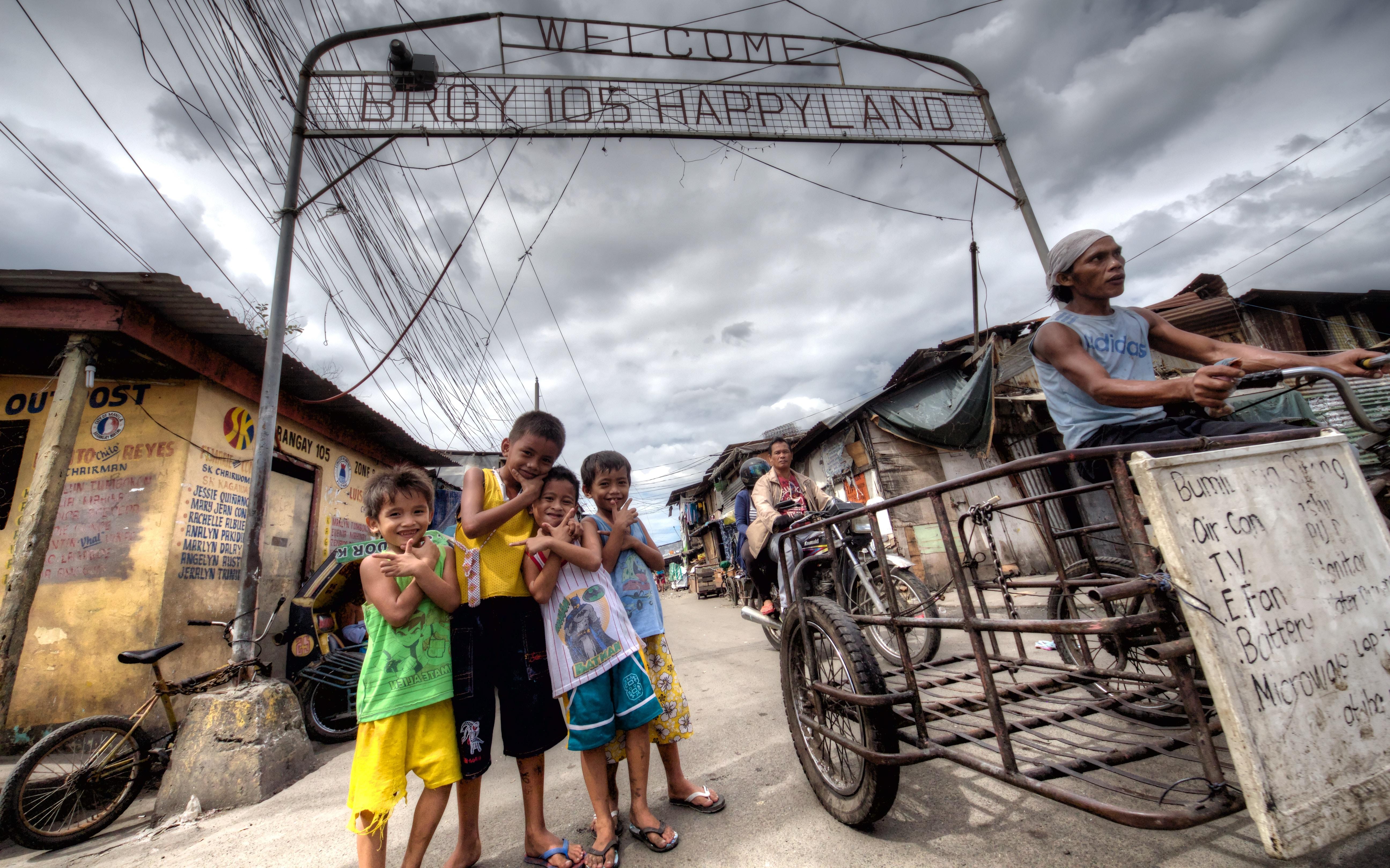 kids taking picture under barangay happyland signage