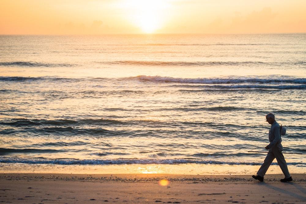 man walking beside ocean at sunset