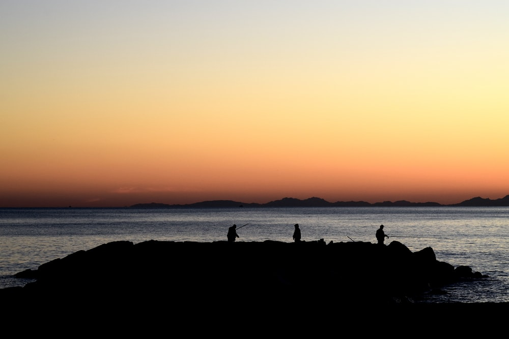 silhouette of three person standing on island during golden hour