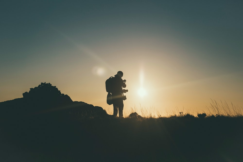 silhouette of mountain climber at golden hour