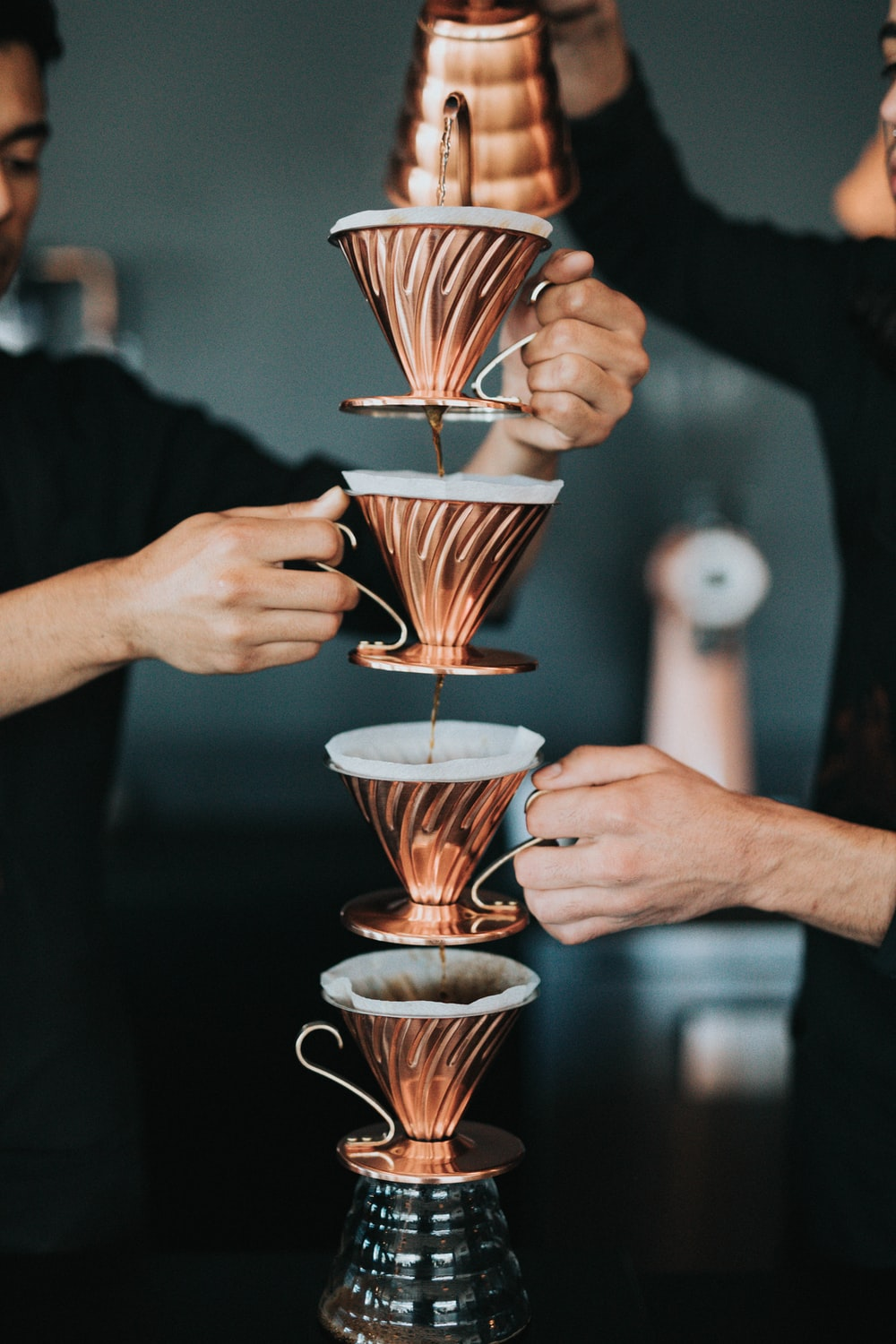 two person pouring coffee with piled cups