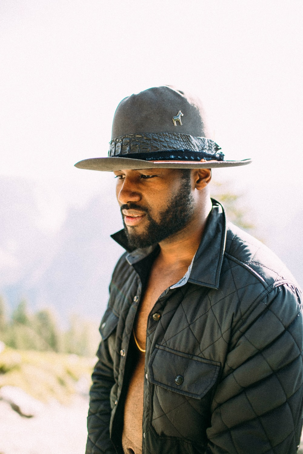 man wearing cowboy hat and buffer jacket looking down outdoor