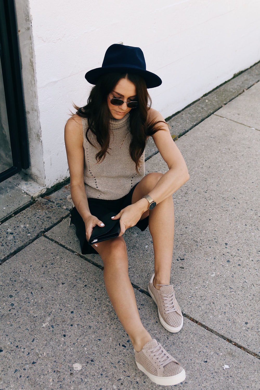 woman sitting on gray concrete pavement beside white wall