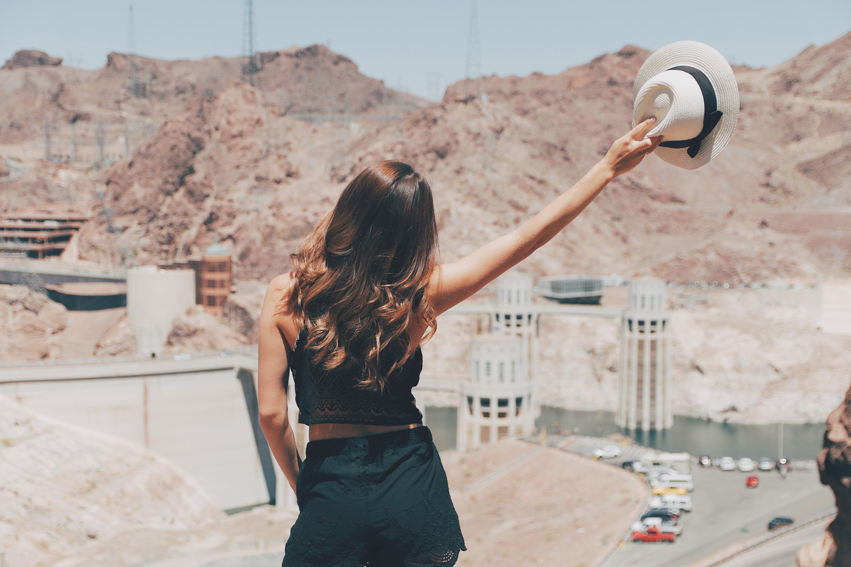 woman raising hat