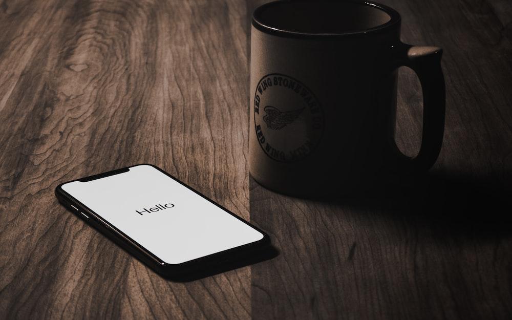 iPhone X on tabletop beside mug