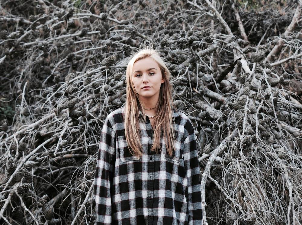 woman standing near driftwood