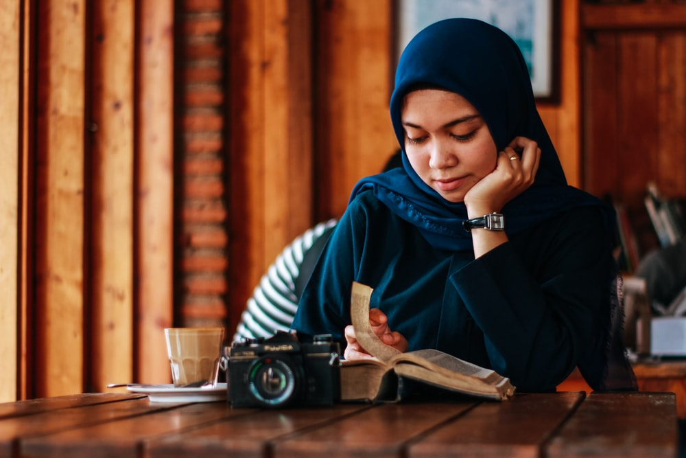 woman sitting beside table reading book