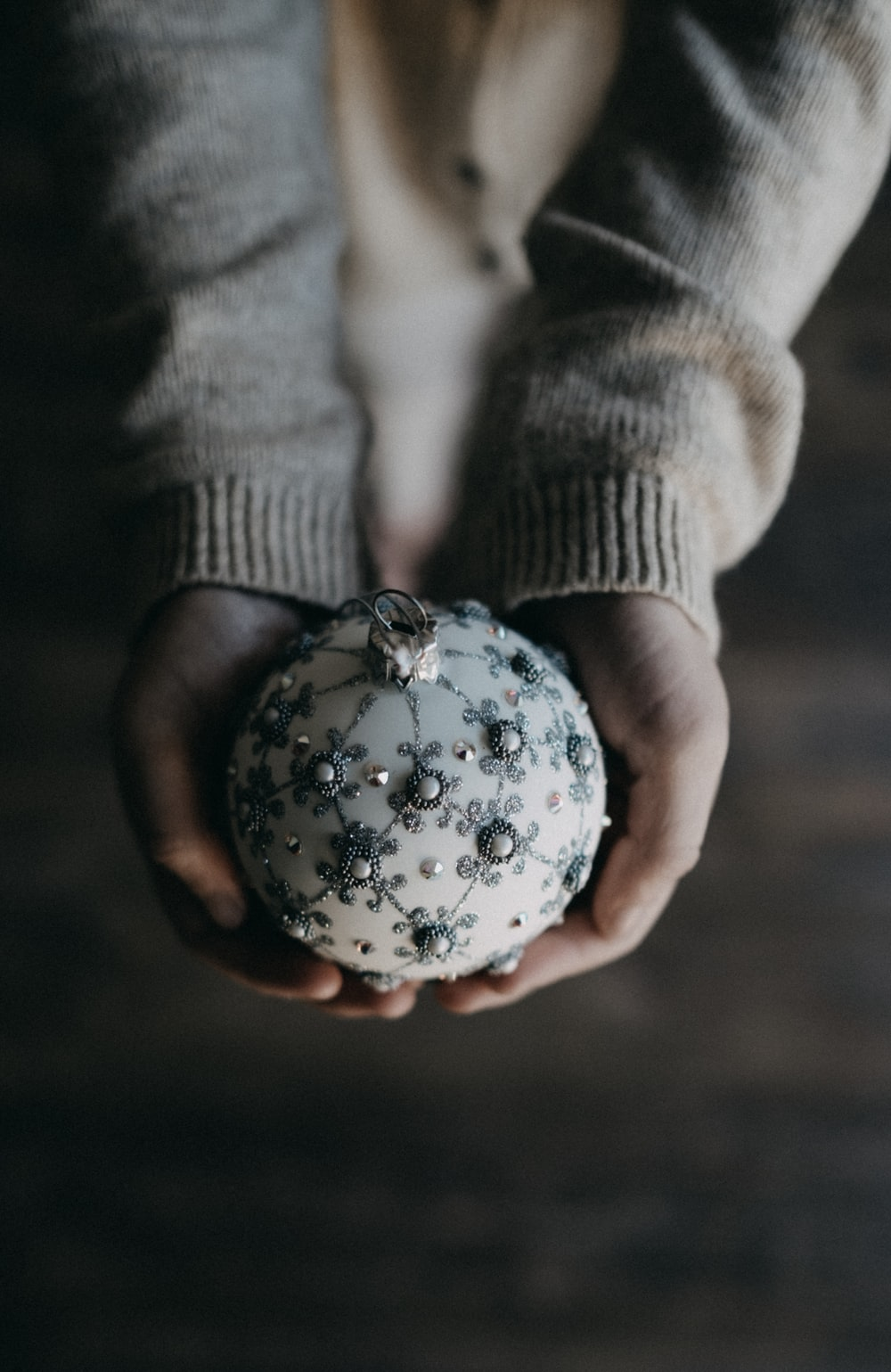 person holding bauble ball