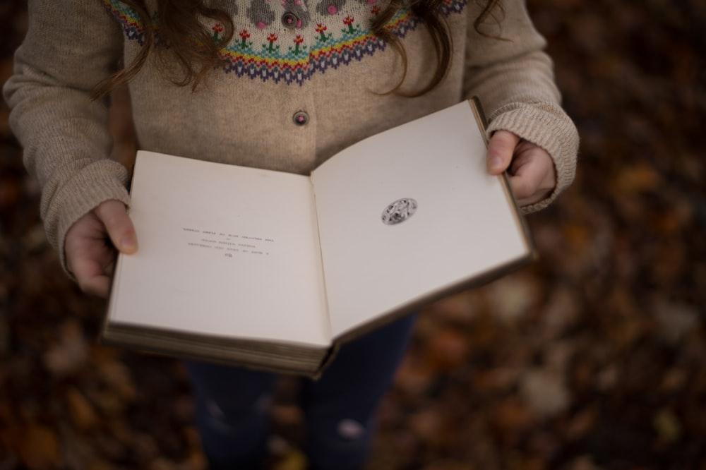 girl reading book closeup photography