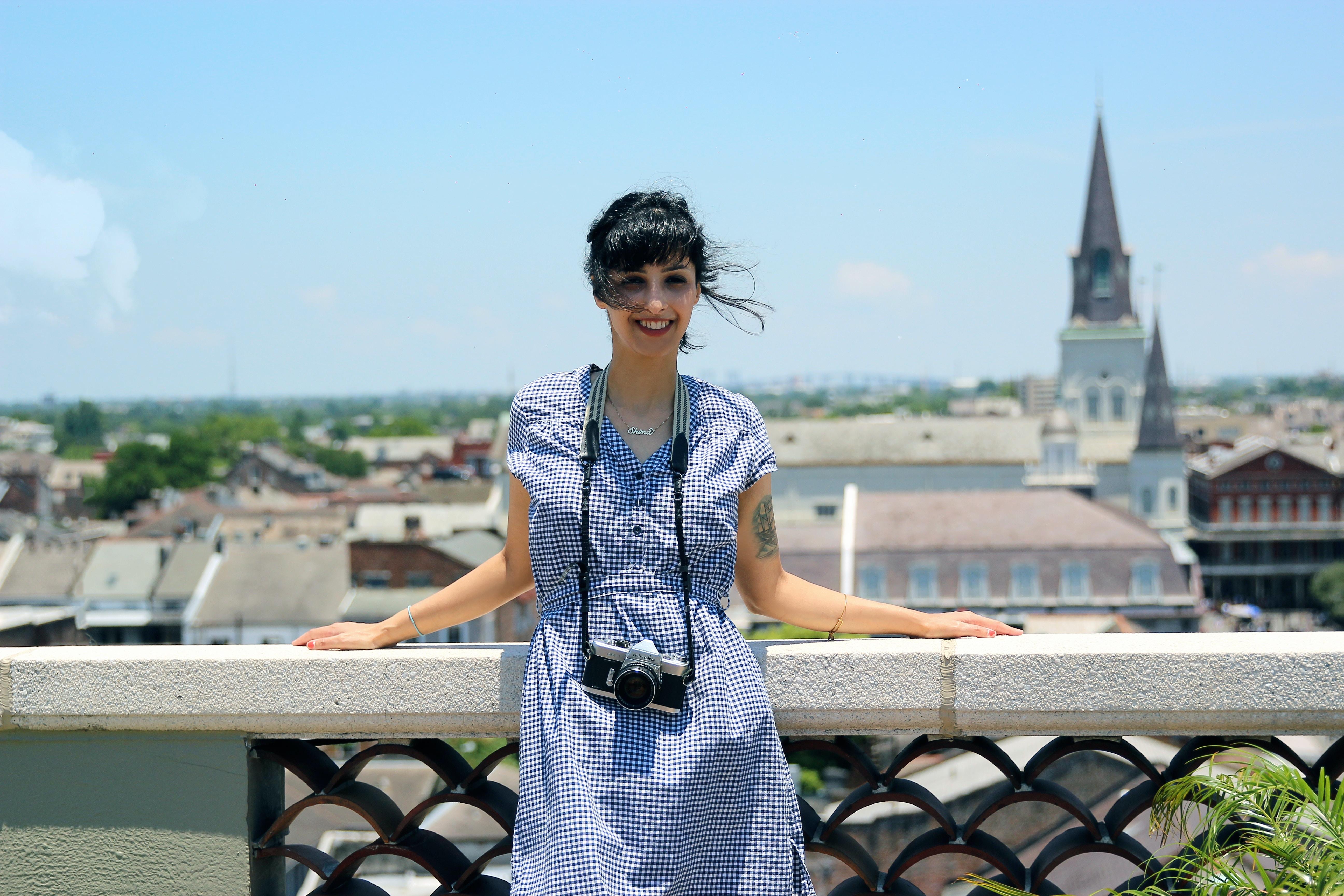 woman wearing blue dress standing beside stand