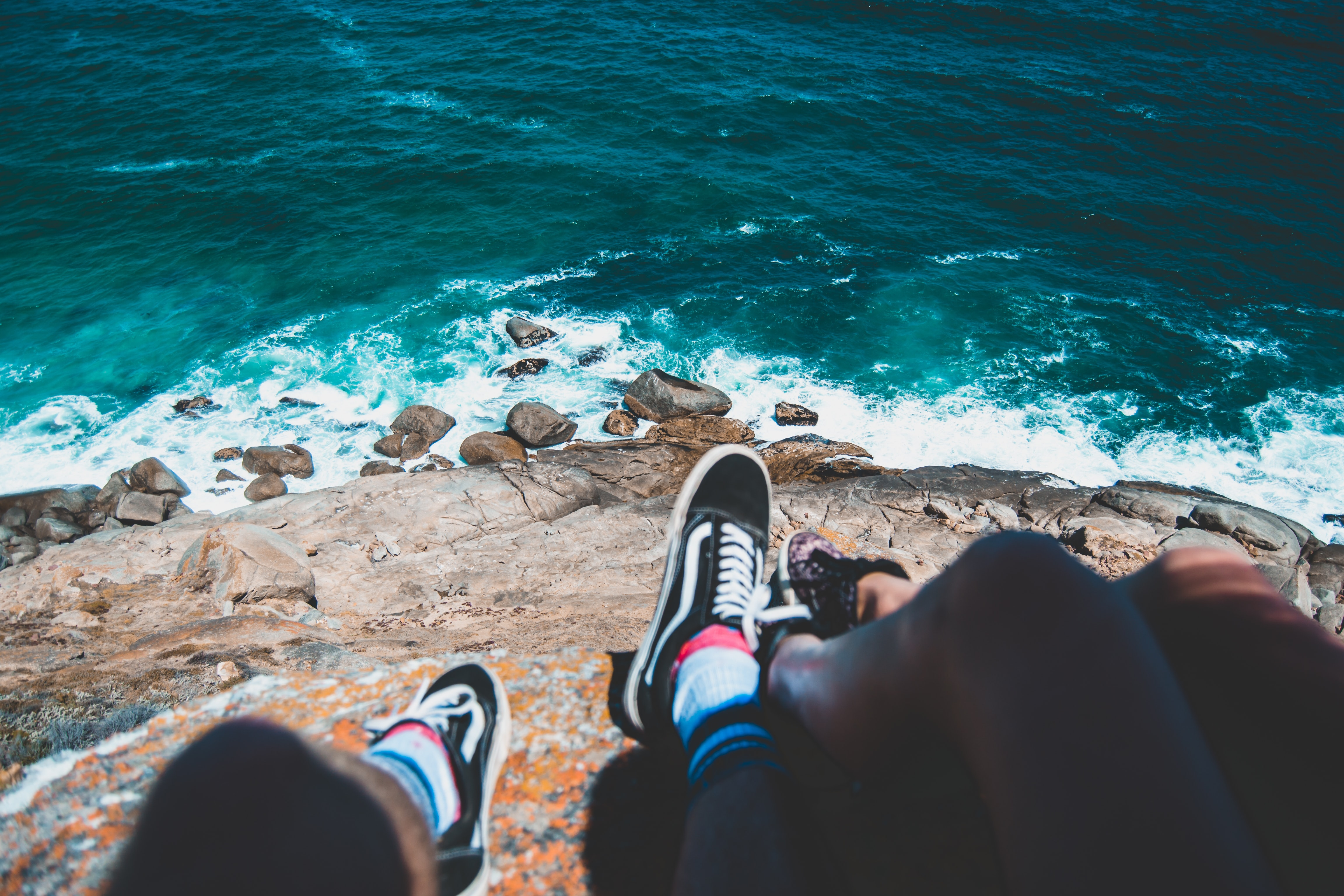 two people sitting on cliff