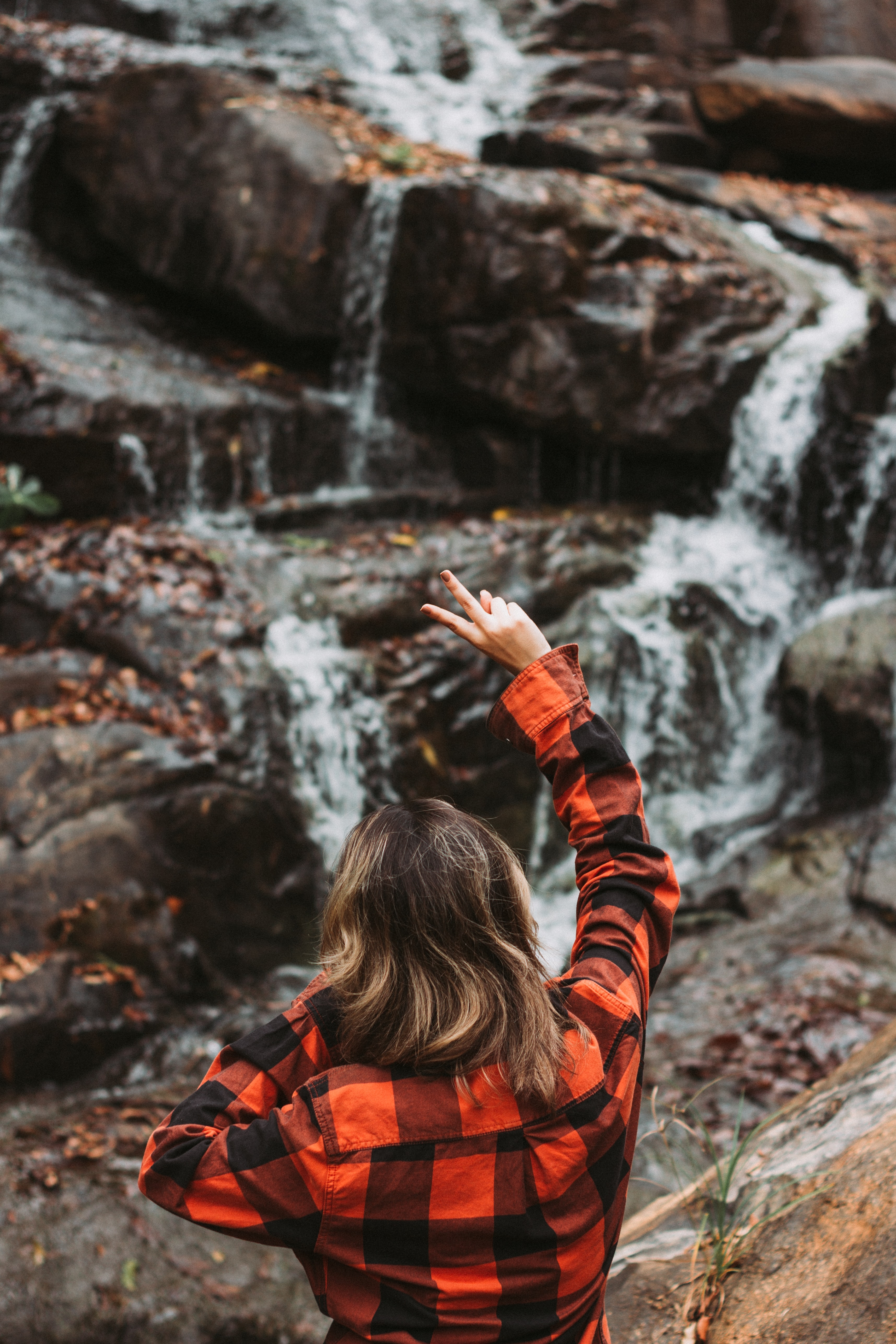 person looking at waterfalls showing peace sign
