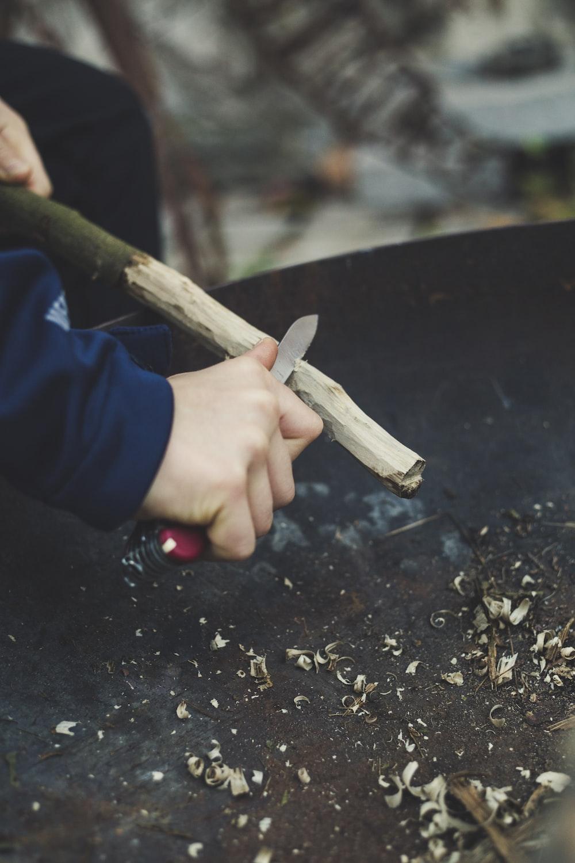 man carving stick