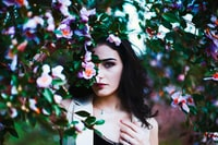 selective focus of woman hiding on flowers during daytime