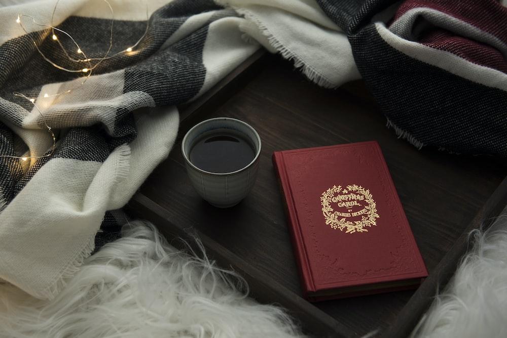 white ceramic coffee mug with coffee besides red envelope