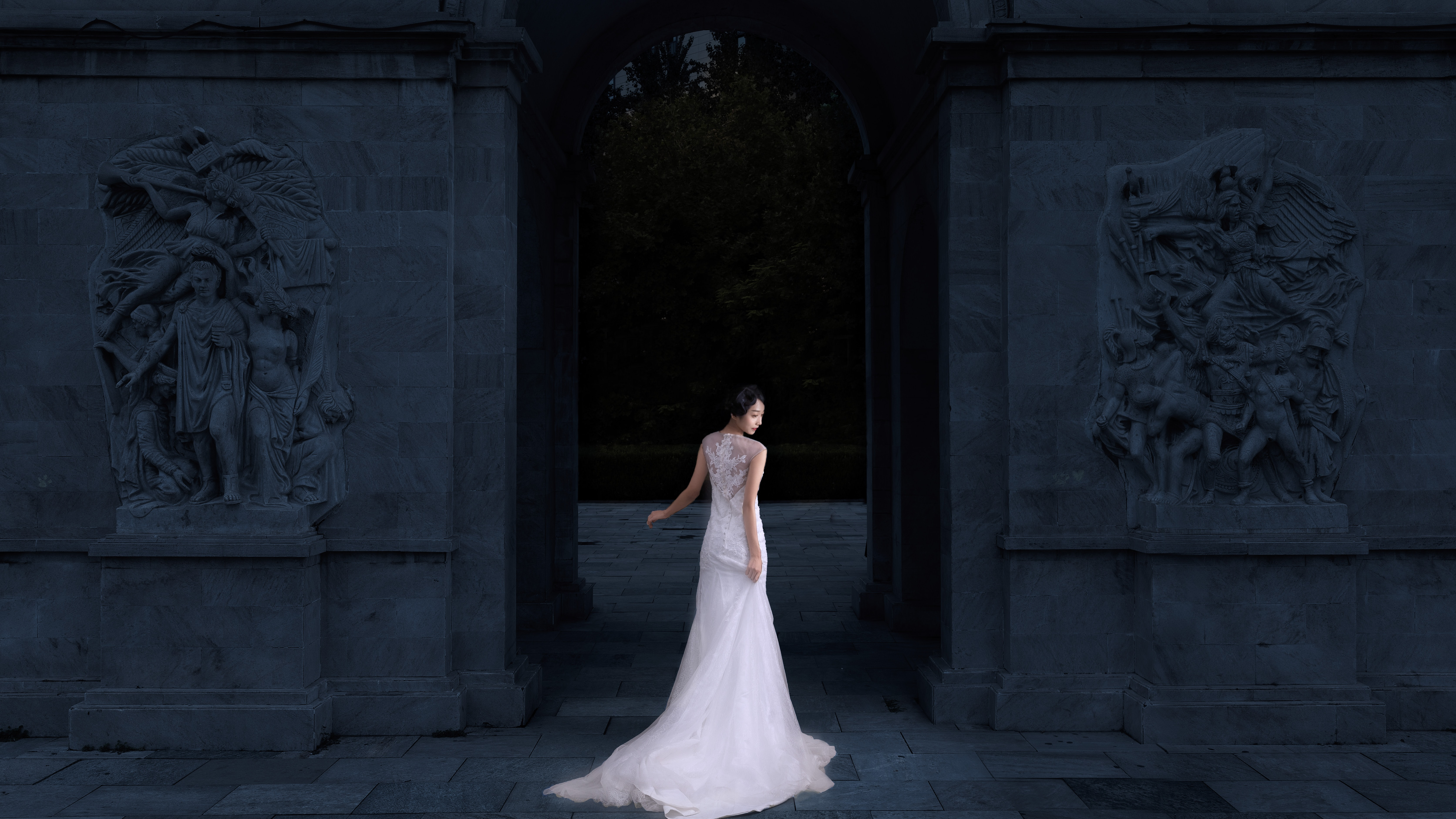 woman wearing white sleeveless wedding gown body facing towards building while face looking sideways