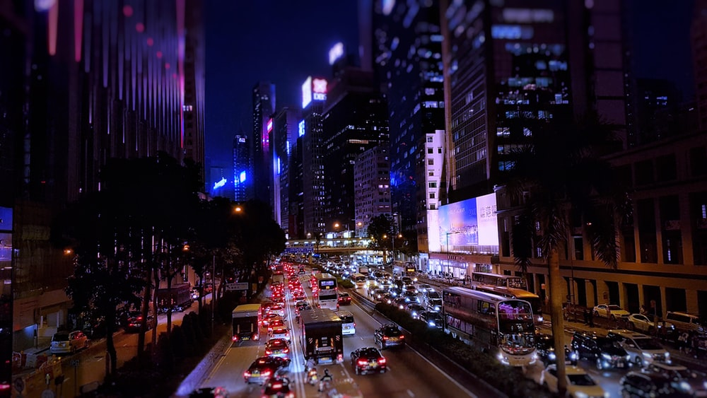 cars travelling on road between buildings at night time