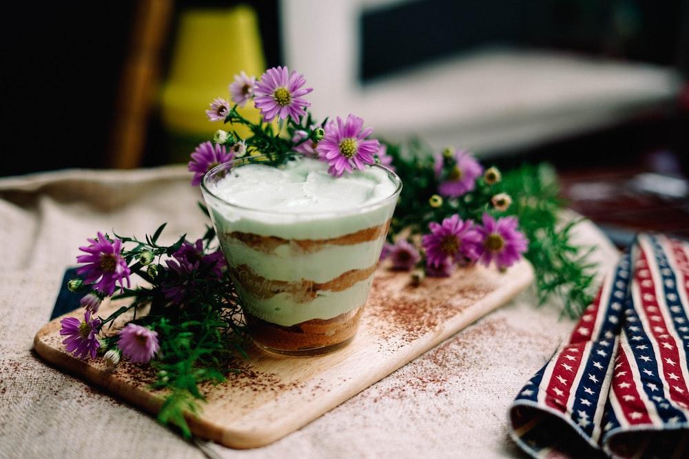 ice cream on drinking glass beside purple flowers