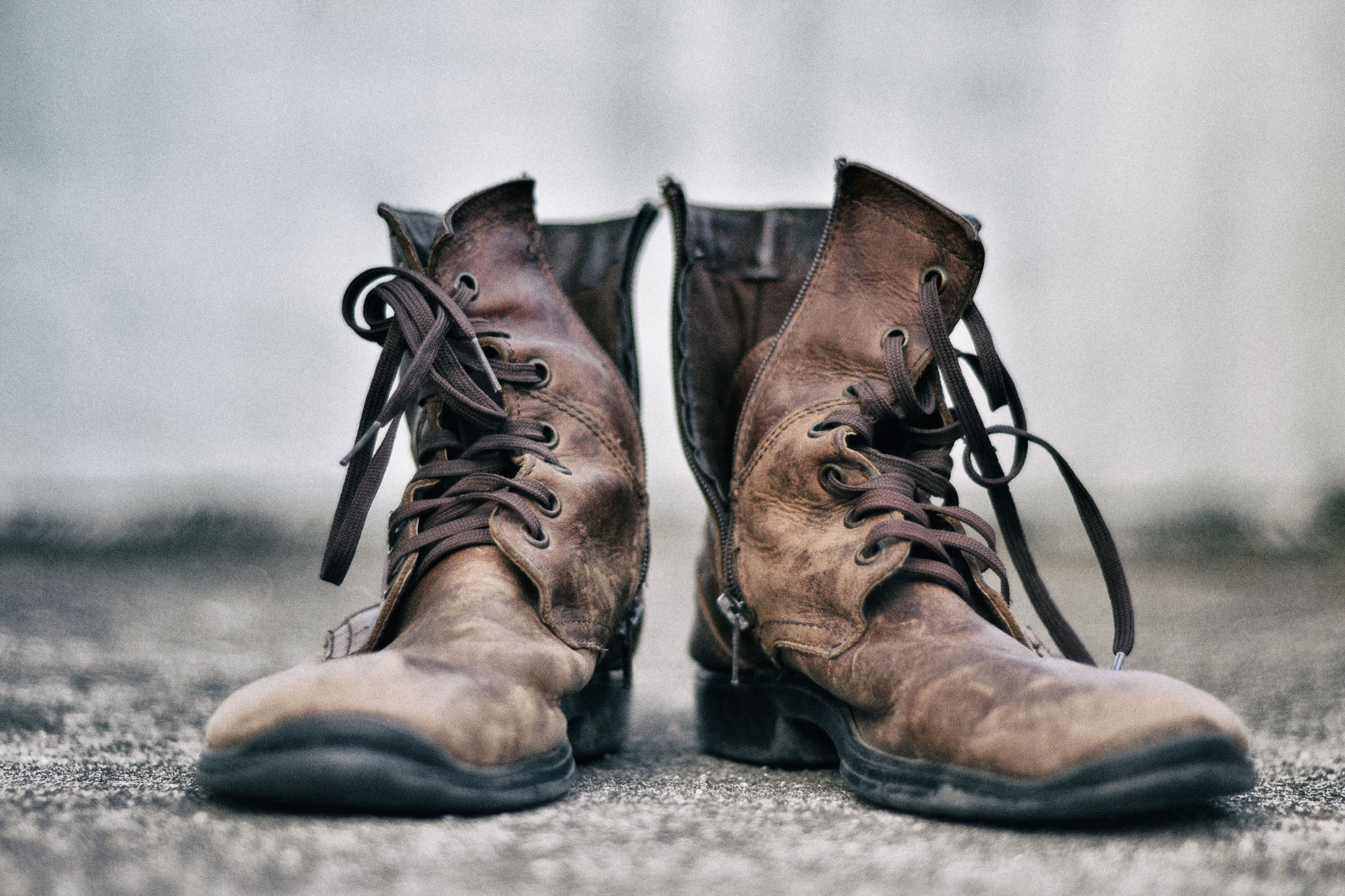 pair of brown leather boots in pavement