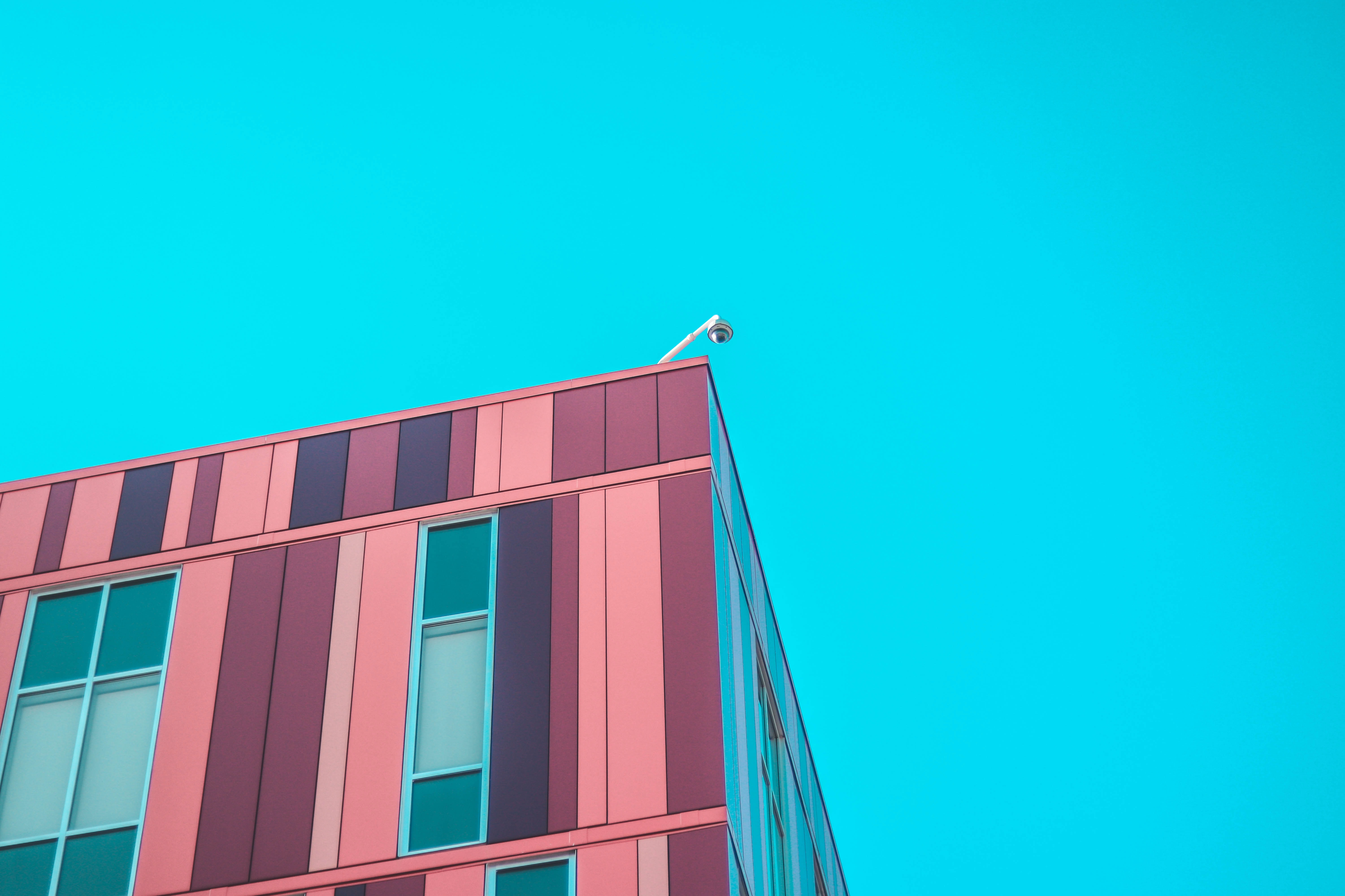 minimalist photography of high-rise building under blue sky