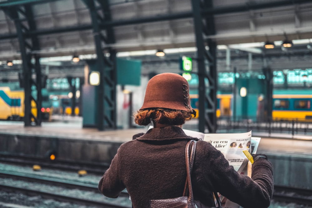 woman holding newspaper beside train rail