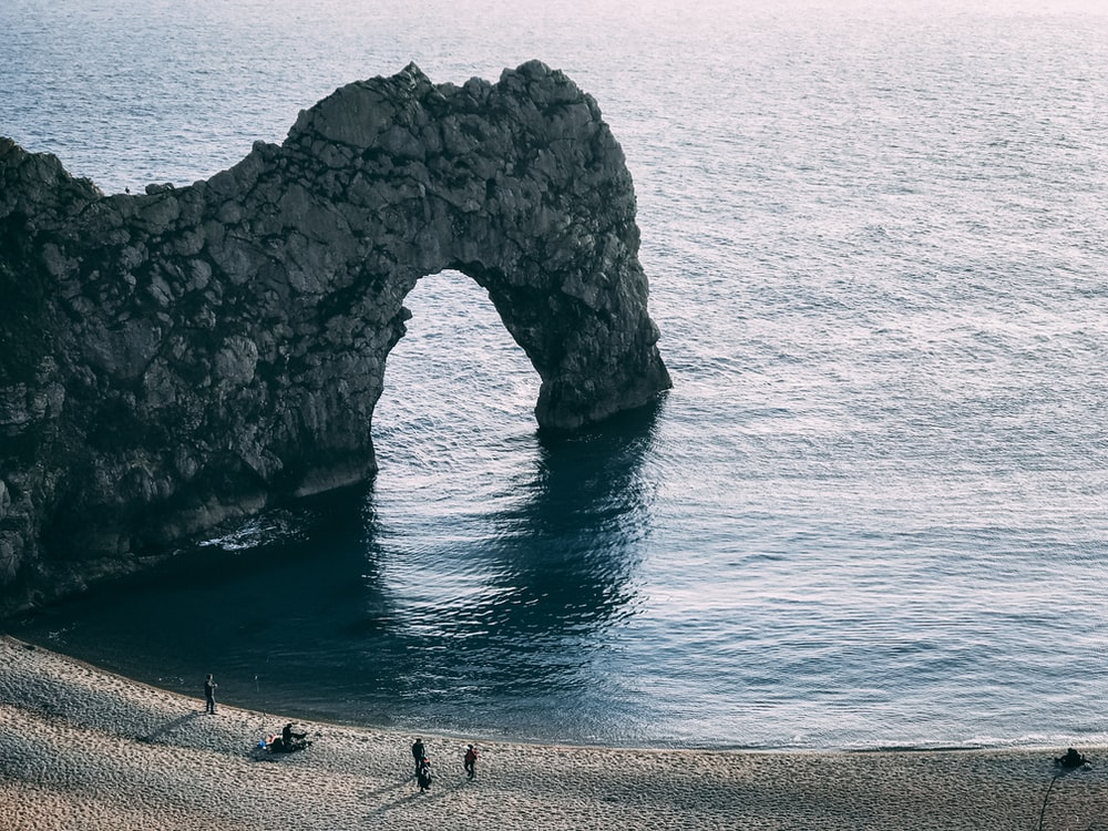 four persons standing on seashore near rock form of arch