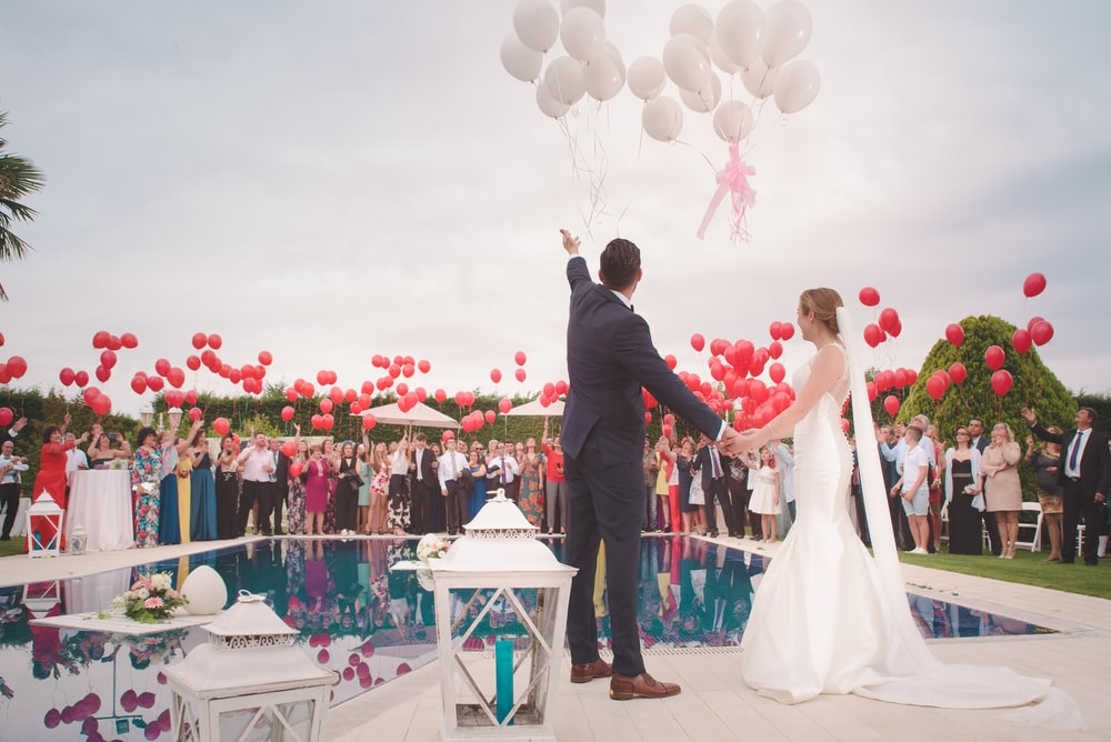 photo of a man and woman newly wedding holding a balloons