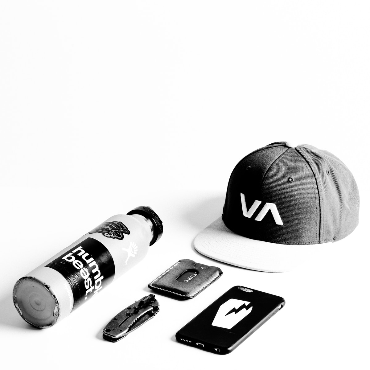 Black and white photograph of a hat, a cellphone, a money clip, a pocket knife and a water bottle.