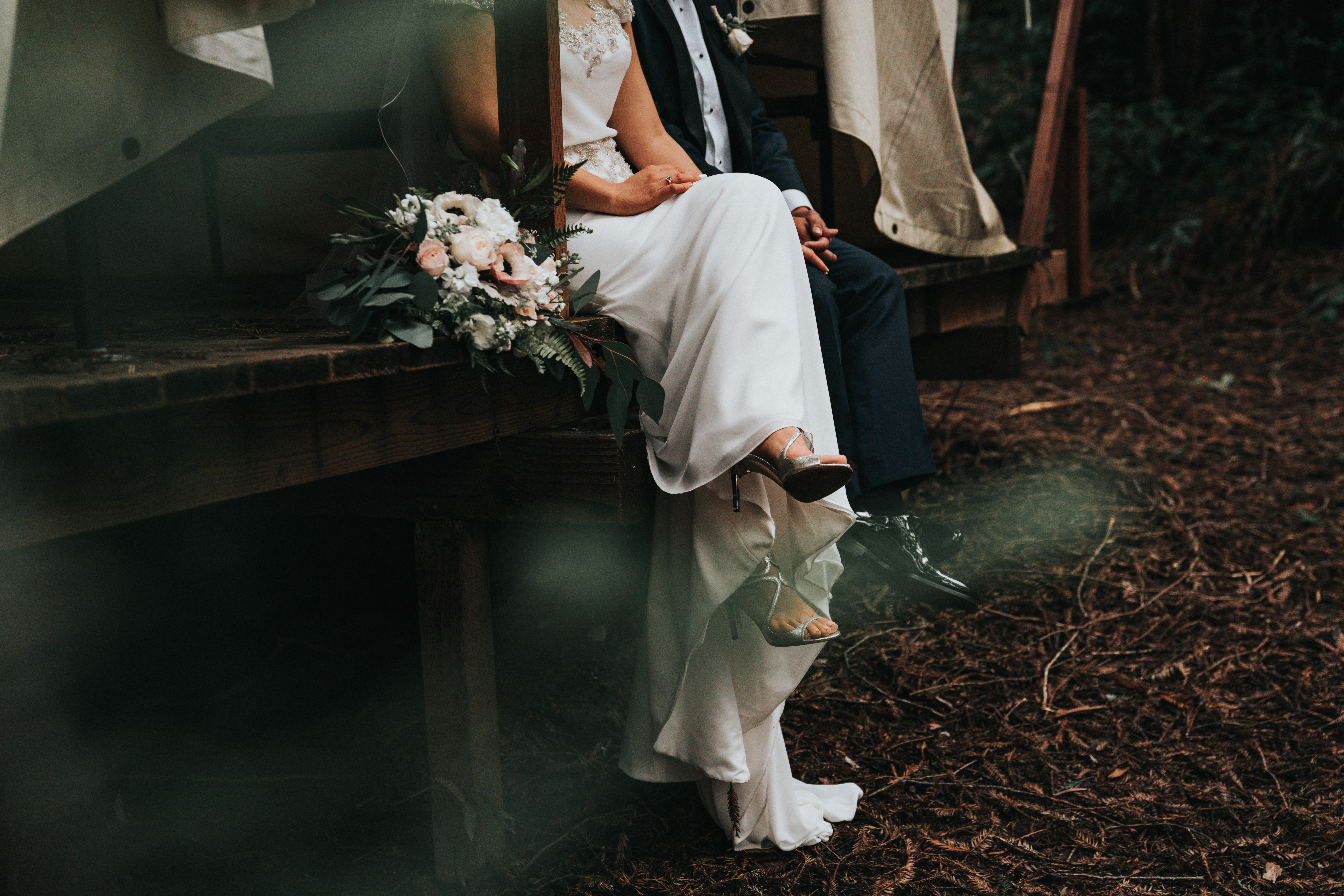 bride and groom sitting and holding their hands