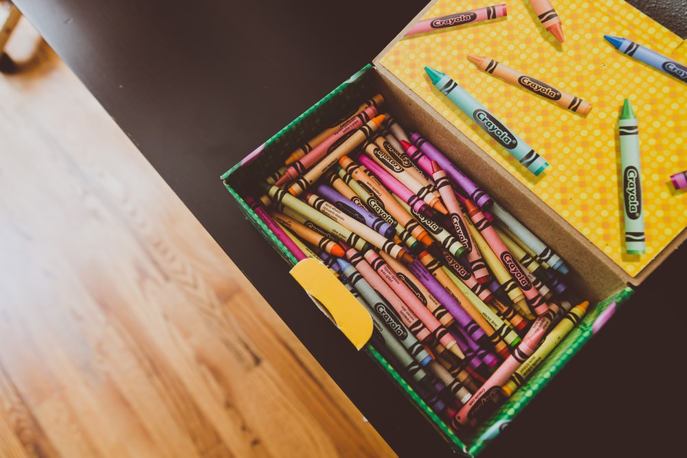 assorted crayons in box on wooden table
