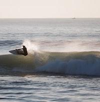 surfer performing tricks on seawave