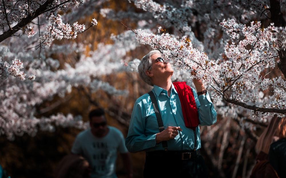 man in teal dress shirt smelling white flower