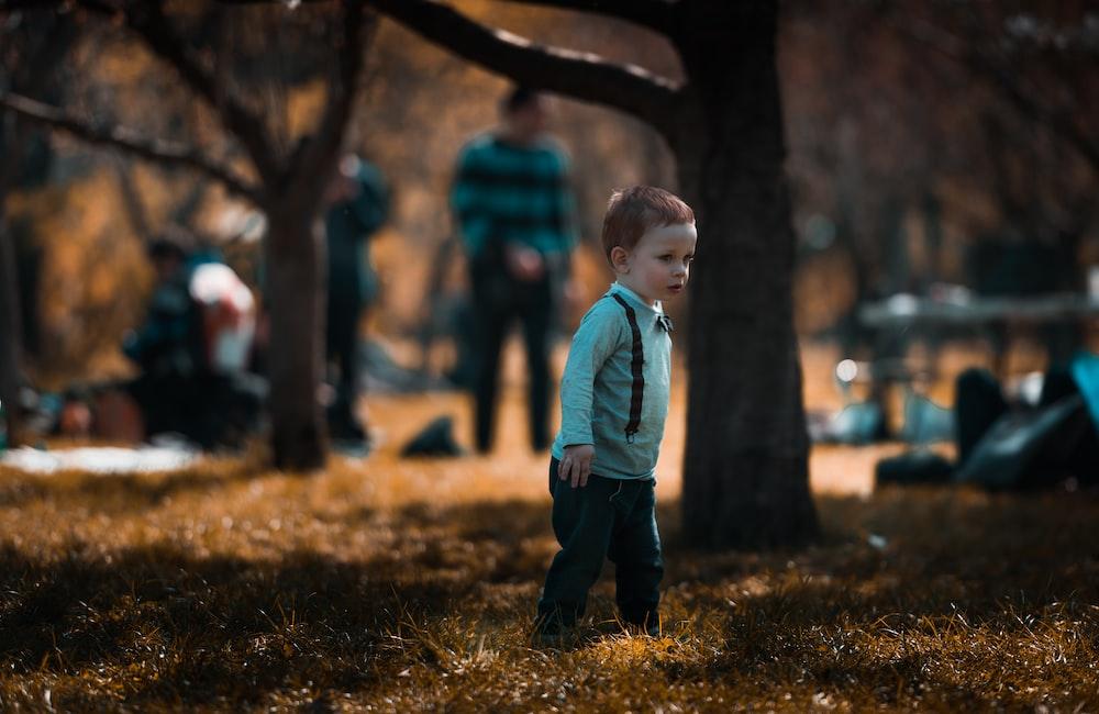 baby boy standing on grass near trees