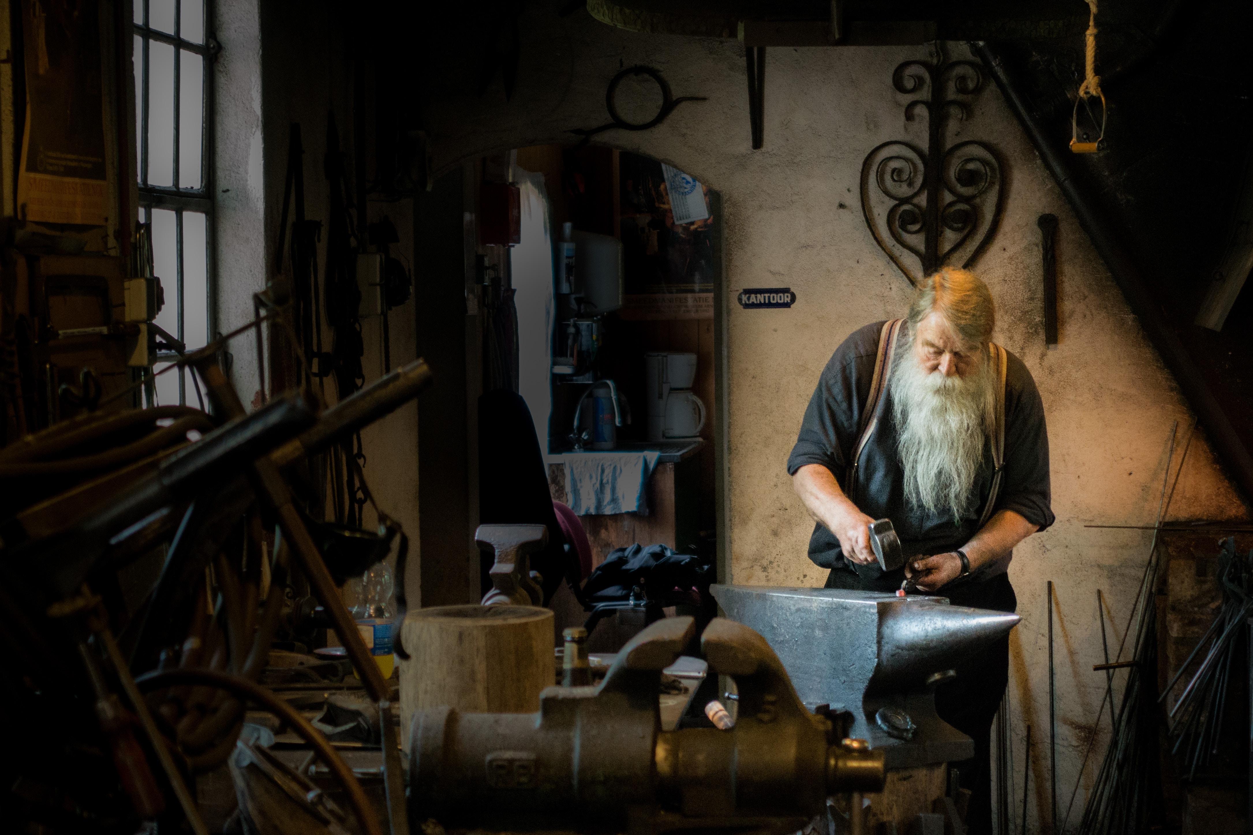 blacksmith holding mallet in garage